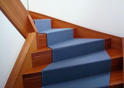 Blaue Teppichstufen auf Holztreppen
